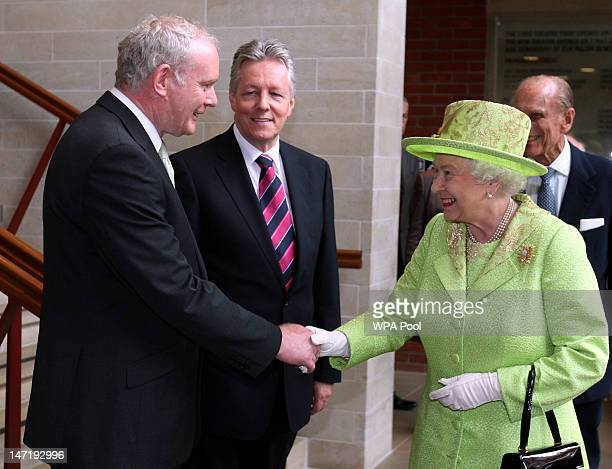 Queen Elizabeth II shakes hands with Deputy First Minister of Northern Ireland Martin McGuinness watched by First Minister Peter Robinson at the...