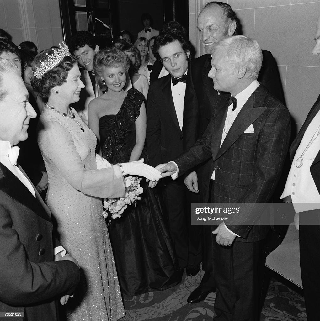 Queen Elizabeth II shakes hands with English comic actor John Inman (1935 - 2007) at the Royal Variety Performance, London, 1981. Left to right: Queen Elizabeth II, singers Alvin Stardust, Lulu and Adam Ant, boxer Henry Cooper and John Inman.