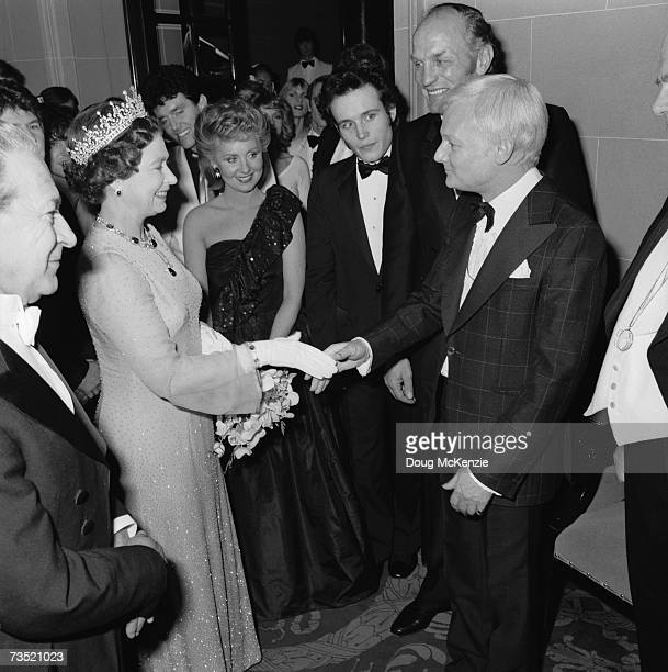 Queen Elizabeth II shakes hands with English comic actor John Inman at the Royal Variety Performance London 1981 Left to right Queen Elizabeth II...