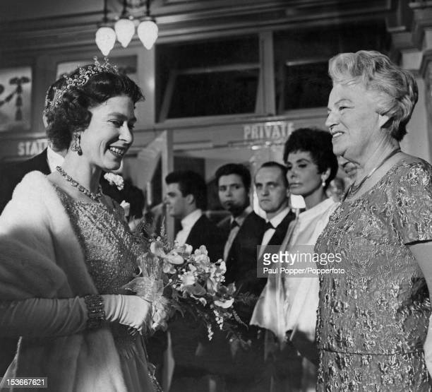 Queen Elizabeth II shakes hands with English singer Gracie Fields at the Royal Variety Performance at the London Palladium 2nd November 1964 Behind...
