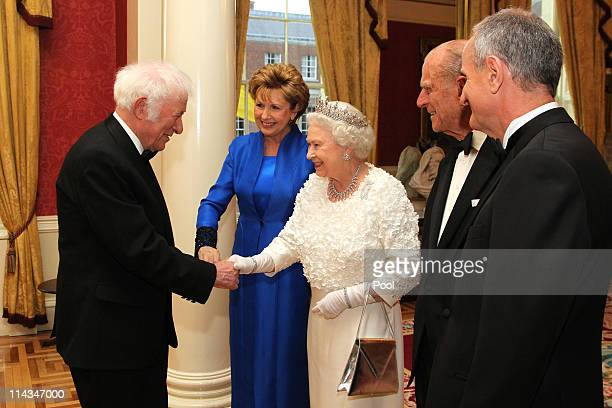 Queen Elizabeth II shakes hands with Irish Poet, Seamus Heaney as Irish President Mary McAleese, Prince Philip, Duke of Edinburgh and Dr. Martin...
