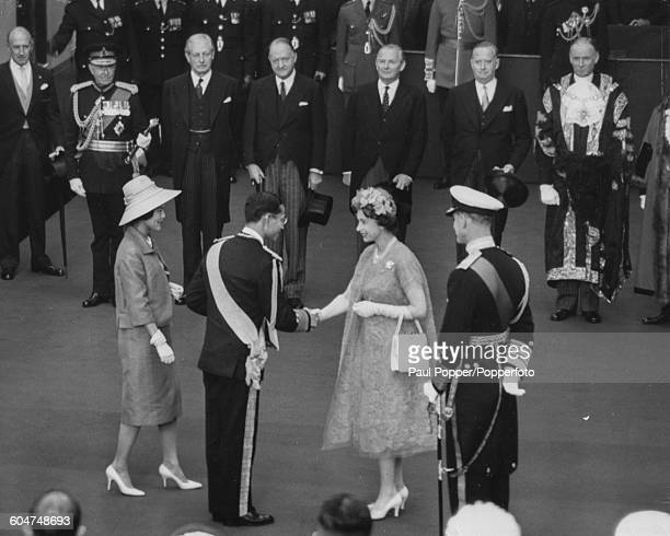Queen Elizabeth II shakes hands with King Bhumibol Adulyadej of Thailand as Queen Sirikit and Prince Philip look on at Victoria Station in London at...