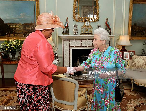 Queen Elizabeth II shakes hands with Mrs Aloun NdombetAssamba the High Commissioner for Jamaica during a private audience at Buckingham Palace on...