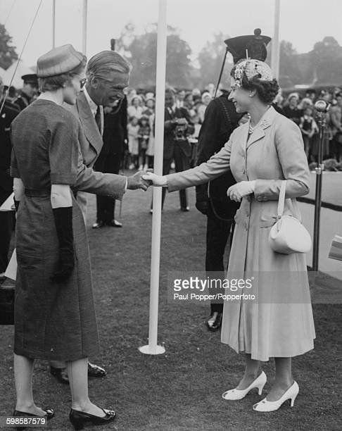Queen Elizabeth II shakes hands with Prime Minister Sir Anthony Eden at a bicentenary celebration and inspection of the King's Royal Rifle Corps...