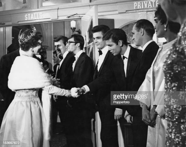 Queen Elizabeth II shakes hands with singer Cliff Richard at the Royal Variety Performance at the London Palladium 2nd November 1964 Left to right...