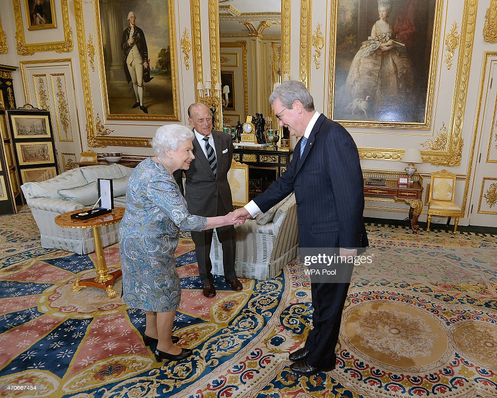 Queen Elizabeth II shakes hands with the Australian High Commissioner Alexander Downer as Prince Philip, Duke of Edinburgh waits to be presented with the Insignia of a Knight of the Order of Australia, in the white drawing room at Windsor Castle on April 22, 2015 in Windsor, England.