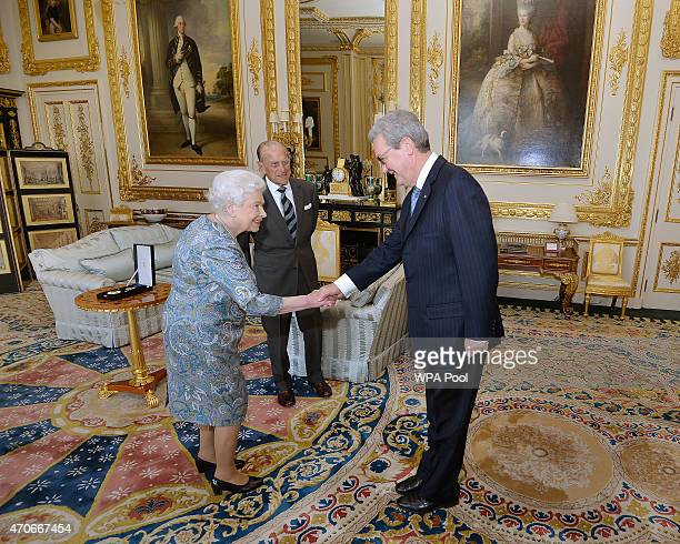 Queen Elizabeth II shakes hands with the Australian High Commissioner Alexander Downer as Prince Philip Duke of Edinburgh waits to be presented with...