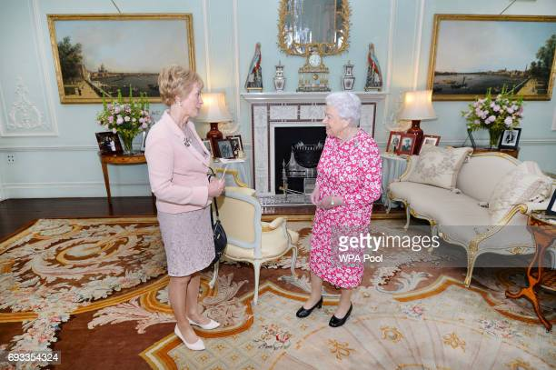 Queen Elizabeth II shakes hands with the Governor of western Australia Kerry Sanderson during at a private audience in Buckingham Palace on June 7...