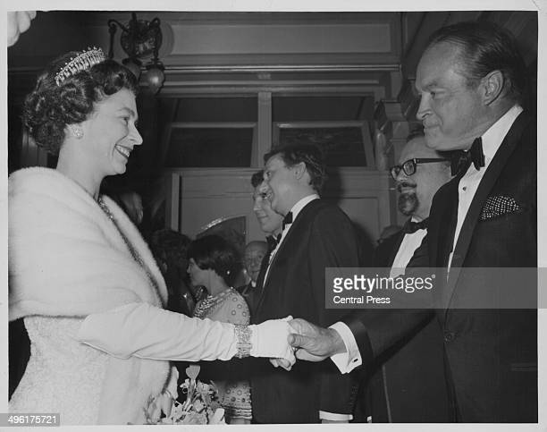 Queen Elizabeth II shaking hands with Bob Hope, with Mireille Mathieu, Ken Dodd and Harry Secombe in the background, at the Royal Variety...