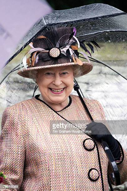 Queen Elizabeth II sheltering under an umbrella joins other members of the Royal Family for Christmas Day service at Sandringham Church on December...
