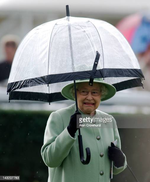 Queen Elizabeth II shelters from the rain at Newbury racecourse on April 21, 2012 in Newbury, England.