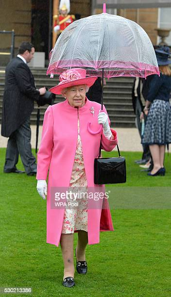 Queen Elizabeth II shelters from the rain under an umbrella during the first Royal Garden Party of the year in the grounds of Buckingham Palace on...