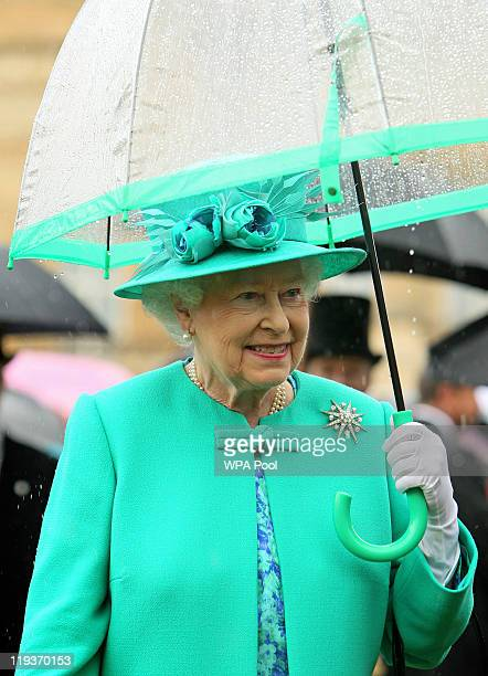 Queen Elizabeth II shelters from the rain under an umbrella while hosting a garden party in the gardens at Buckingham Palace on July 19 2011 in...
