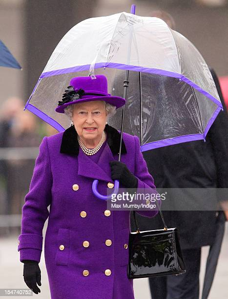 Queen Elizabeth II shelters under an umbrella as attends the opening of the newly developed Jubilee Gardens on October 25 2012 in London England