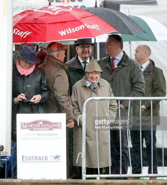 Queen Elizabeth II shelters under an umbrella as she attends day 1 of the Royal Windsor Horse Show in Home Park on May 8, 2019 in Windsor, England.