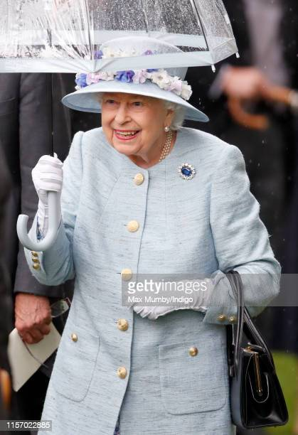 Queen Elizabeth II shelters under an umbrella as she attends day two of Royal Ascot at Ascot Racecourse on June 19, 2019 in Ascot, England.