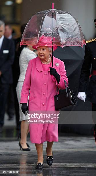 Queen Elizabeth II shelters under an umbrella as she visits the newly redeveloped Birmingham New Street Station on November 19 2015 in Birmingham...