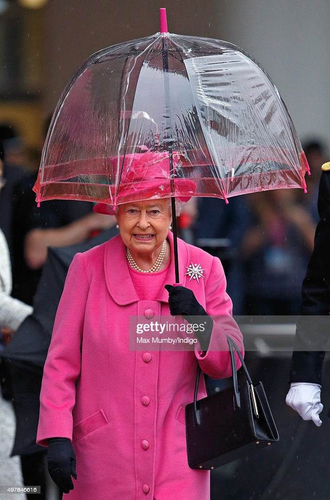 Queen Elizabeth II shelters under an umbrella as she visits the newly redeveloped Birmingham New Street Station on November 19, 2015 in Birmingham, England.