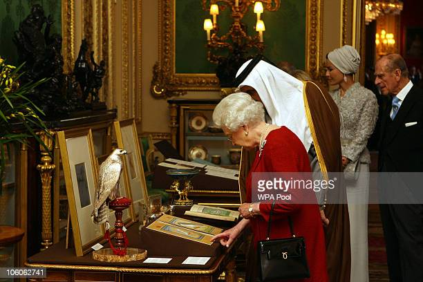 Queen Elizabeth II shows the Emir of Qatar Sheikh Hamad bin Khalifa alThani around exhibits from the Royal Collection with one of his three wives...