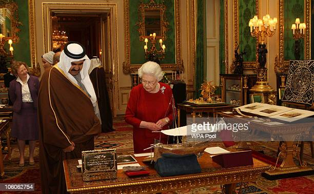 Queen Elizabeth II shows the Emir of Qatar Sheikh Hamad bin Khalifa alThani around exhibits from the Royal Collection at Windsor Castle during his...