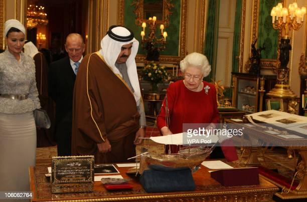 Queen Elizabeth II shows the Emir of Qatar Sheikh Hamad bin Khalifa alThani around exhibits with one of his three wives Sheikha Mozah bint Nasser...