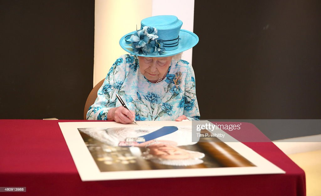 Queen Elizabeth II signing a portrait of herself at the Broadway Theatre on July 16, 2015 in Barking, United Kingdom.