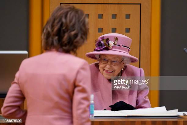Queen Elizabeth II signs a commemorative parchment in the Senedd inside the Siambr during the ceremonial opening of the Sixth Senedd at The Senedd on...