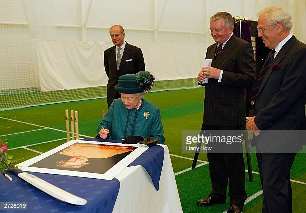 Queen Elizabeth II signs a portrait of herself and a cricket bat for display while HRH Prince Phillip, ECB Chairman David Morgan and Loughborough...