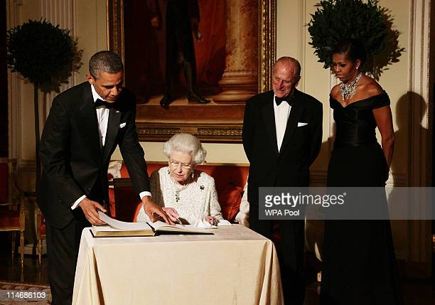Queen Elizabeth II signs the guest book as she bids farewell to US President Barack Obama and First Lady Michelle Obama watched by the Duke of...