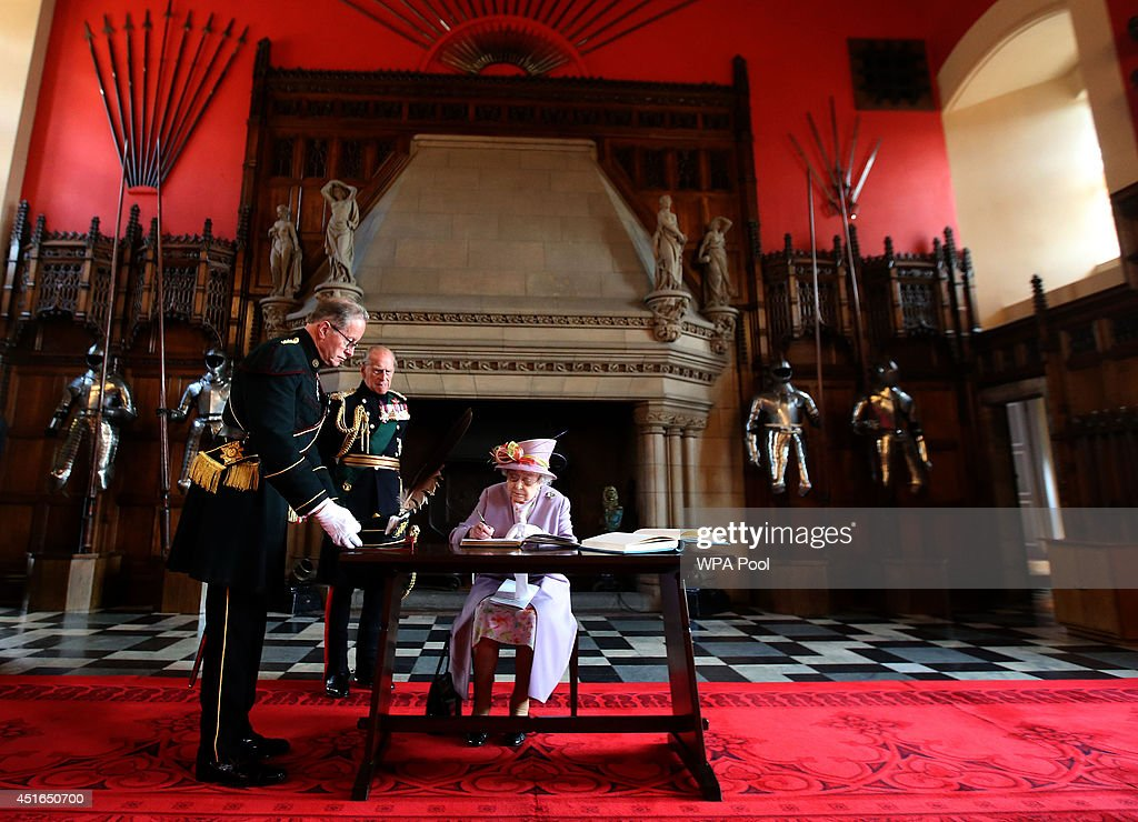 Queen Elizabeth II signs the guest book at the Great Hall at Edinburgh Castle after attending a commemorative service for the Scottish National War Memorial at Edinburgh Castle on July 3, 2014 in Edinburgh, Scotland.