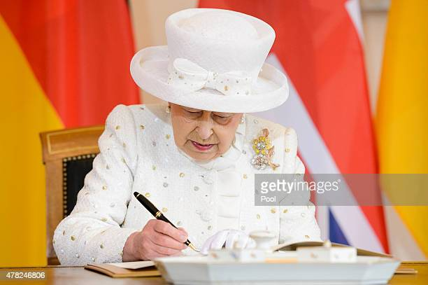 Queen Elizabeth II signs the guest book at the Schloss Bellevue Palace on the second day of a four day State visit to Germany on June 24 2015 in...