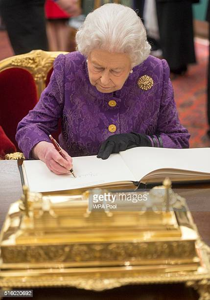Queen Elizabeth II signs the guest book during a reception for the High Commissioners' Banquet to mark Commonwealth Week at the Guildhall on March 16...