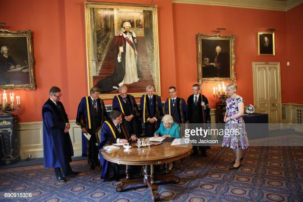 Queen Elizabeth II signs the Instrument which is a document written on vellum and formally records Her Majesty's attendance at the lunch to celebrate...