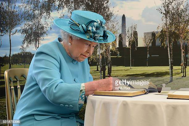 Queen Elizabeth II signs the visitor book following a service paying tribute to soldiers from the Duke of Lancaster's Regiment killed while serving...