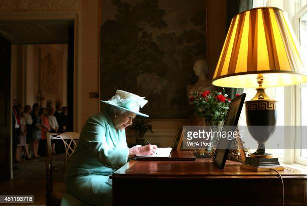 Queen Elizabeth II signs the visitor book prior to departing Hillsborough Castle on the third and final day of the Queen's visit to Northern Ireland...