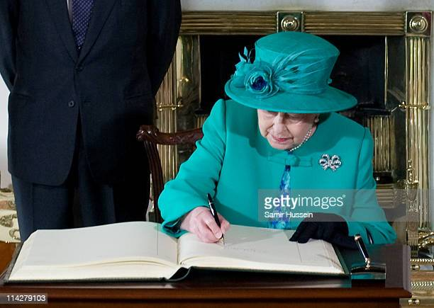 Queen Elizabeth II signs the visitors book at Aras an Uachtarain with Prince Philip, Duke of Edinburgh and Martin McAleese on May 17, 2011 in Dublin,...