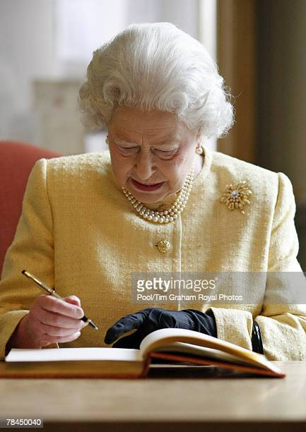 Queen Elizabeth II signs the visitors book during a tour of the Royal Academy of Music on December 13, 2007 in London, England.