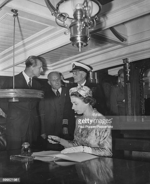 Queen Elizabeth II signs the visitors book in the captain's cabin aboard the 'Cutty Sark' sailing ship the last of the tea clippers as Prince Philip...