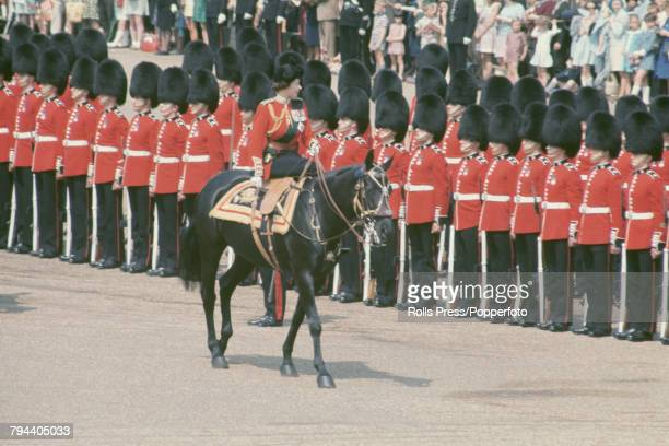 Queen Elizabeth II sits astride her horse Burmese as she makes her way past a line of British Army Foot Guards on Horse Guards Parade during the...
