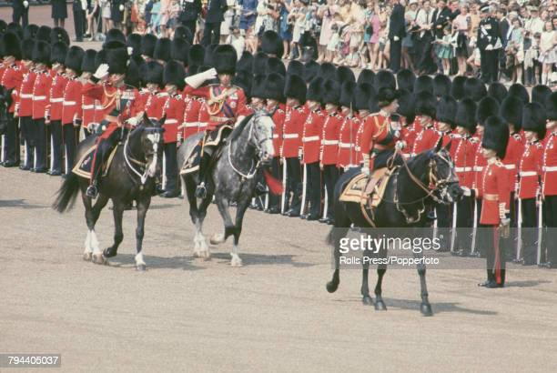 Queen Elizabeth II sits astride her horse Burmese followed by Prince Philip Duke of Edinburgh as she makes her way past a line of British Army Foot...