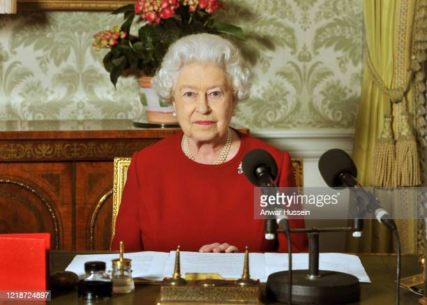 Queen Elizabeth II sits at her desk with microphones at Buckingham Palace after recording her Commonwealth Day address that is broadcast across the...