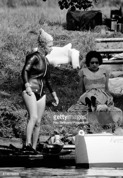 Queen Elizabeth II sits back whilst her sister Princess Margaret wearing a wetsuit prepares to waterski at Sunninghill Park Windsor on 25th July 1964...