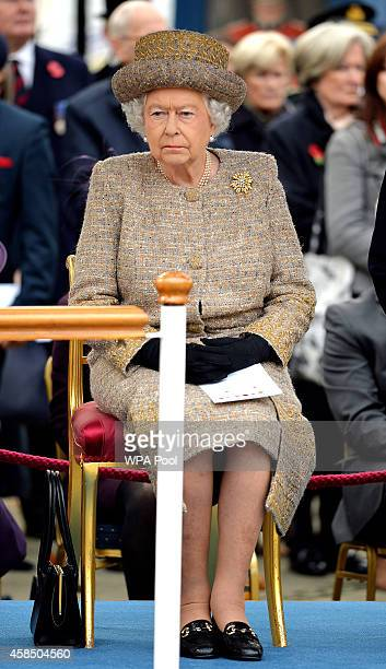 Queen Elizabeth II sits before she places a wreath of poppies at the new Flanders Field Memorial outside the Guards Chapel on November 6 2014 in...