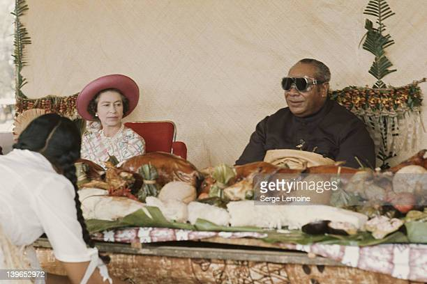 Queen Elizabeth II sits down to a Maori banquet during her visit to New Zealand 1977