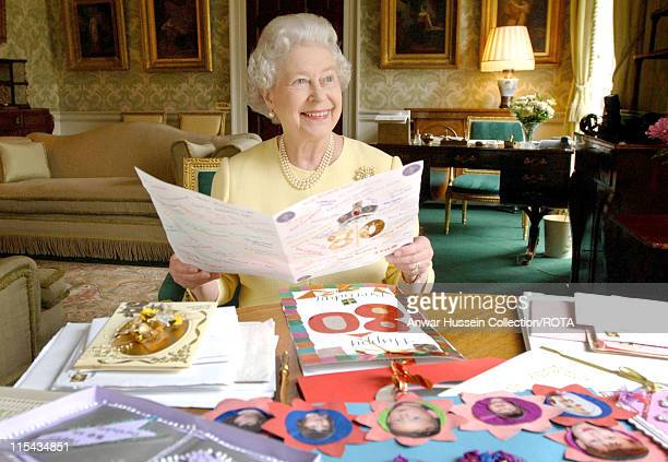 Queen Elizabeth II sits in the Regency Room at Buckingham Palace in London, April 20 as she looks at some of the cards which have been sent to her...