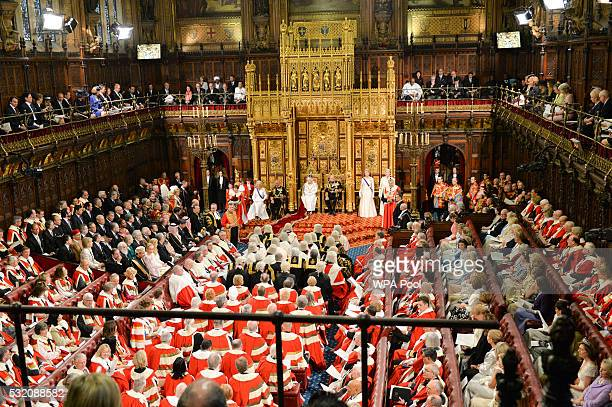 Queen Elizabeth II sits on the throne beside Prince Philip Duke of Edinburgh Prince Charles Prince of Wales and Camilla Duchess of Cornwall during...