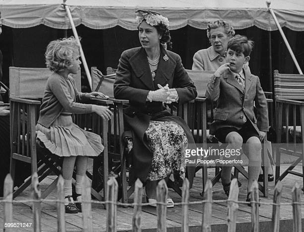 Queen Elizabeth II sits with her children Princess Anne and Prince Charles as they watch the Duke of Edinburgh play polo on Smith's Lawn in Windsor...