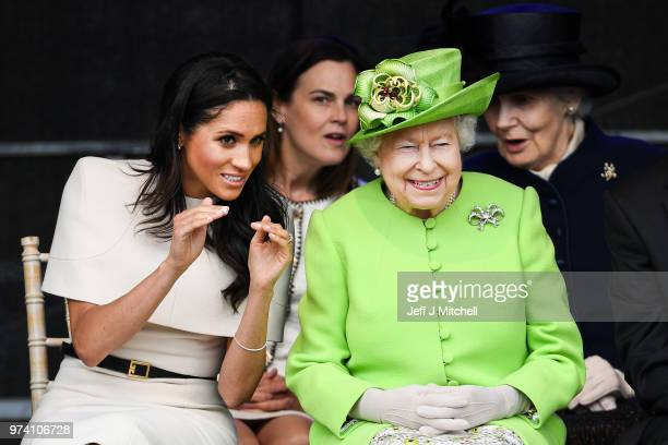 Queen Elizabeth II sitts and laughs with Meghan Duchess of Sussex accompanied by Samantha Cohen during a ceremony to open the new Mersey Gateway...