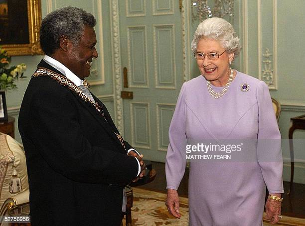 Queen Elizabeth II smiles after investing GovernerGeneral of the Solomon Islands Sir Nathaniel Waena as a Knight Grand Cross of the Order of St...