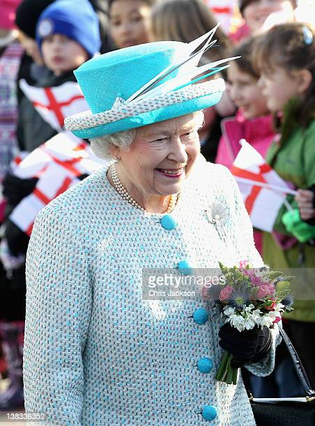 Queen Elizabeth II smiles as children wave flags during a visit to Dersingham School on February 6 2012 in King's Lynn England The Queen made the...